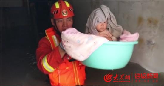 小区遭大水围困 消防员用盆端出小宝宝